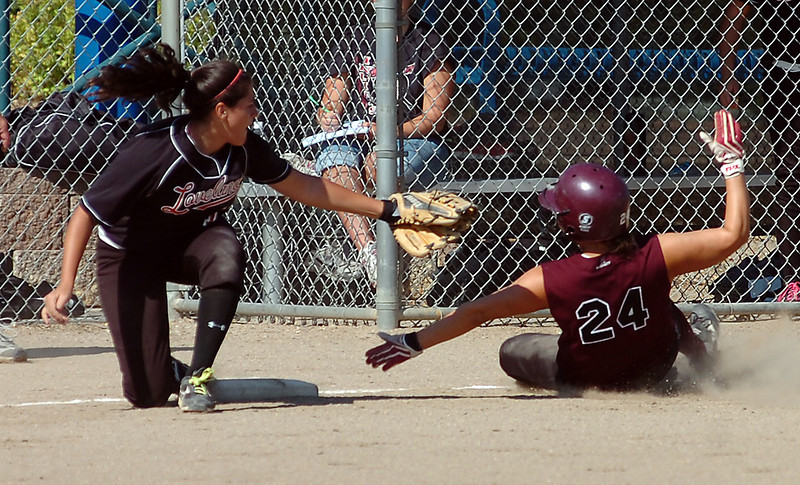 Loveland's #12 Samantha Villarreal tries to tag out Berthoud's #24 at third base during their game at Centennial Field in Loveland Tuesday.