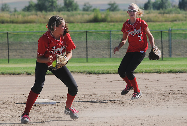 Loveland High School shortstop Cassidy Smith, left, fields a ground ball while teammate Annika Anderson looks on in the bottom of the third inning of a game against Mountain View at MVHS. The Mountain Lions won, 3-0.