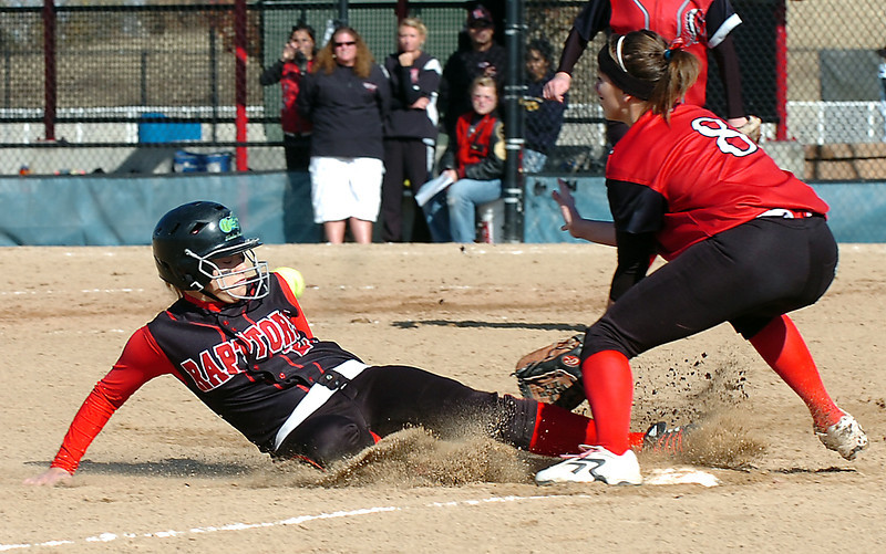 Loveland's #8 Amanda Farrell prepares to catch the ball as Eaglecrest's #20 Bekah Matthews slides into third base during their game Friday at the Aurora Sports Park.