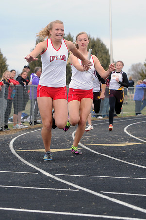 Loveland High School's Celine Packham, left, accepts the baton from teammate Rae McCloughan while competing in a heat of the 400-meter relay during the Max Marr Invitational on Saturday, April 13, 2013 at Berthoud High School.