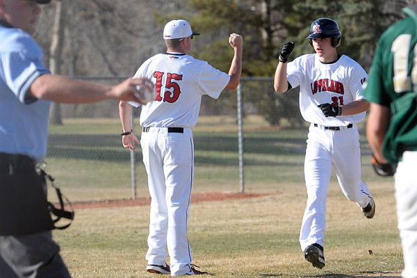 Loveland High School's Kake Weinmaster (31) is congratulated by coach Jake Marshall while rounding third base after hitting a home run in the bottom of the fourth inning of a game against Bear Creek on Thursday, April 4, 2013 at Centennial Field.