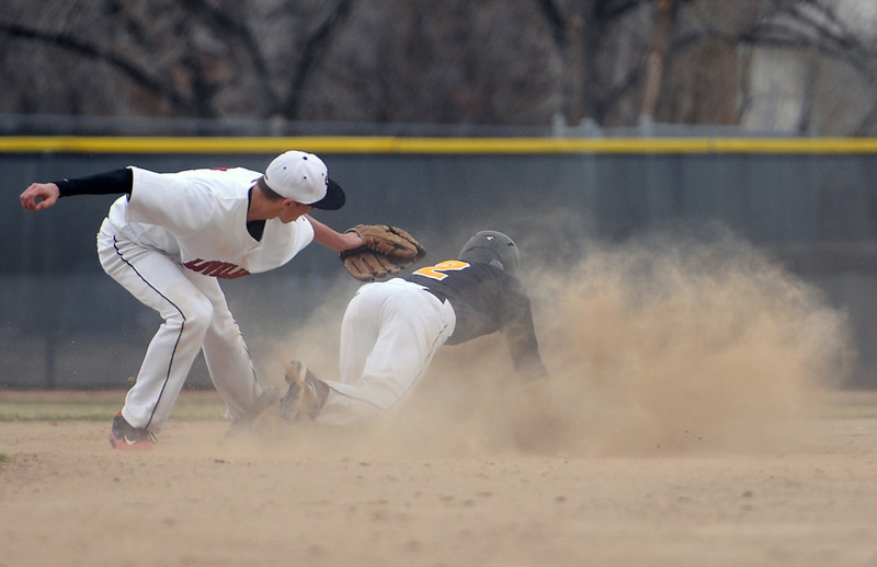Loveland High School senior JC Schneider tags out Thompson Valley senior Sam Hardy at second base Monday evening during the fifth inning of a frigid and windy baseball game played at Bill Swift Field in Loveland, Colo.