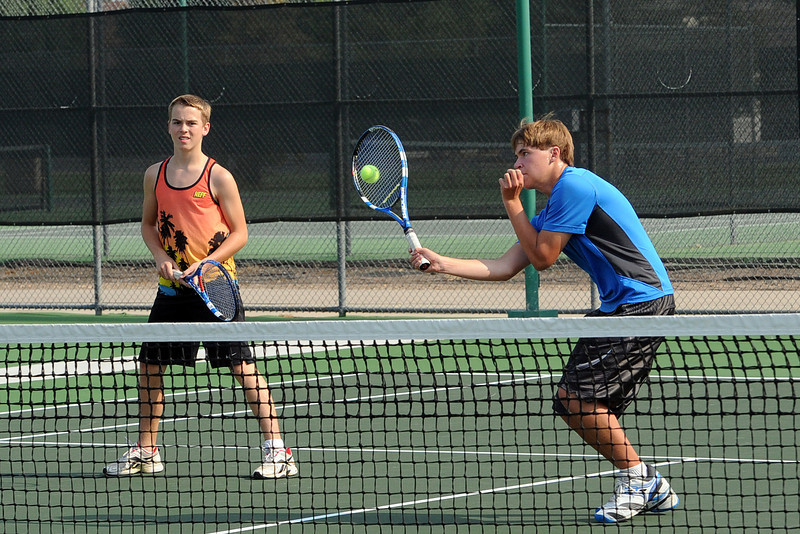 Loveland High School sophomore Sam Hecker, right, hits a volley while teammate Tanner Foster looks on during round-robin play at practice Friday, Aug. 17, 2012 at the North Lake Park tennis courts.