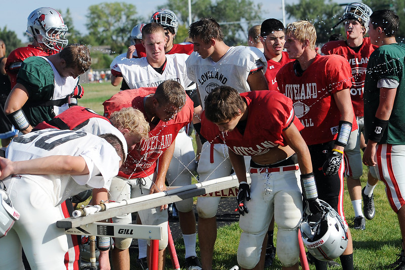 Loveland High School football players take a water break during practice Wednesday, Aug. 29, 2012 at LHS.