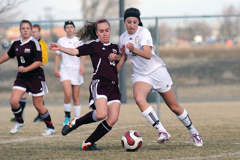 Loveland High School senior Allison Gleason, right, collides with Berthoud sophomore Courtney DeMoudt as they converge on the ball in the second half of their match on Thursday, March 28, 2013 at the Mountain View soccer field.