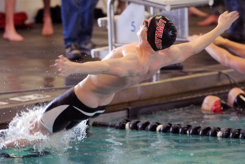 Loveland High School's Ryan Ball dives into the pool at the start of the 100-yard backstroke during a meet Tuesday, March 12, 2013 at the Mountain View Aquatic Center.