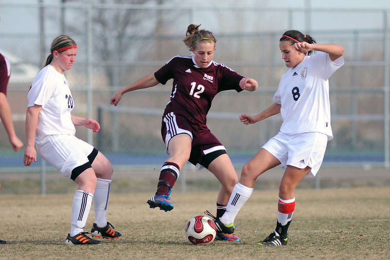 Berthoud High School senior Lindsey Loberg, middle, battles for control of the ball between Loveland's Jordan Rausch, left, and Kat Bossenbroek in the second half of their match on Thursday, March 28, 2013 at the Mountain View soccer field.