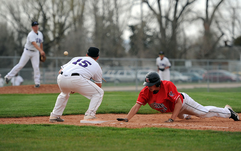 Loveland High School sophomore K.C. Pomponio dives back to first before Mountain View High School sophomore Ozzie Pearcy can tag him out in the fifth inning of a game played at MVHS, Monday afternoon in Loveland, Colo.