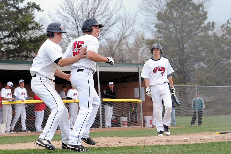 Loveland High School teammates Jake Weinmaster, left, and Jay Larson congratulate each other after scoring two runs in the bottom of the sixth inning of their game against Fossil Ridge on Tuesday, April 30, 2013 at Swift Field.