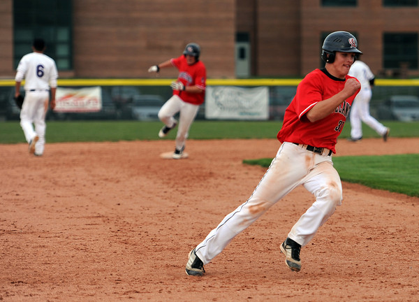 Loveland High School sophomore Jake Weinmaster, right, rounds third base during the seventh inning of a baseball game at MVHS, Monday evening in Loveland, Colo.