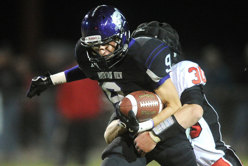Mountain View High School senior Connor Logan (9) is tackled by Loveland's Jake Weinmaster after making a catch in the second quarter of their game on Friday, Nov. 2, 2012 at Patterson Stadium.