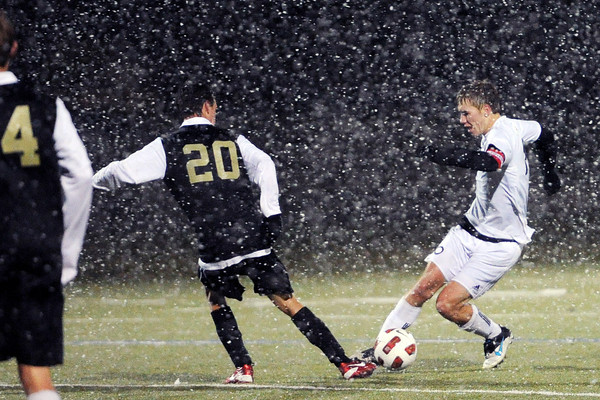 Loveland High School's Brian Strasbaugh, right, dribbles around Rock Canyon defender Kyle Huebsch during the first half of their match Wednesday, Oct. 24, 2012 at the Loveland Sports Park.
