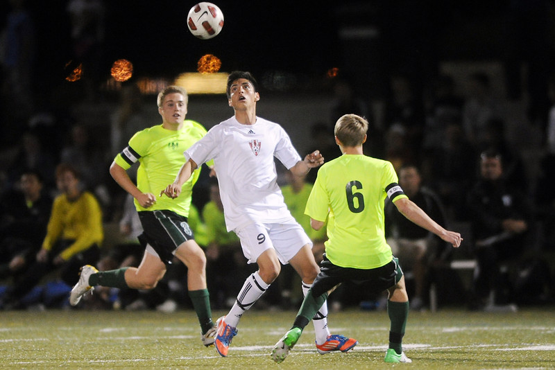 Loveland High School's Cristian Buendia, middle, tracks down the ball between Fossil Ridge's Hunter Robinson, left, and Nate Blank in the first half of their match on Tuesday, Oct. 16, 2012 at the Loveland Sports Park.