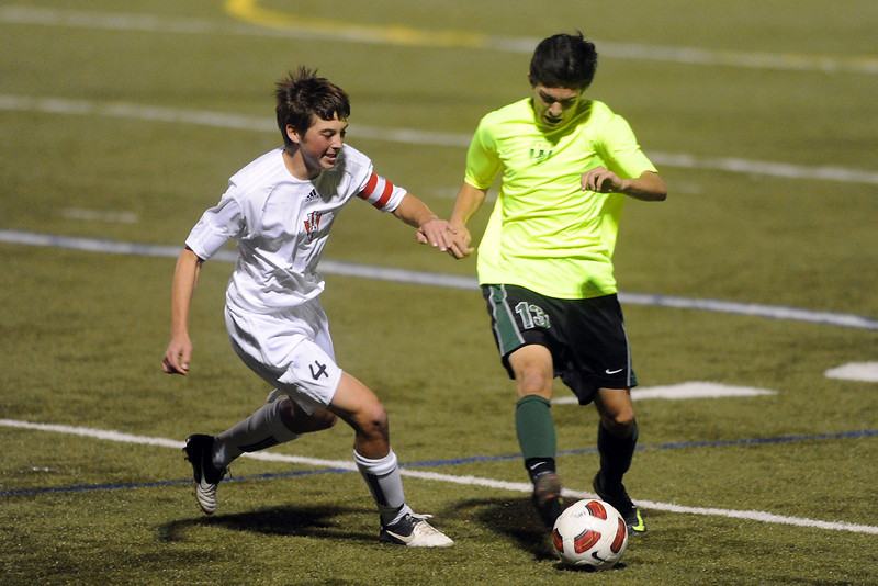 Loveland High School defender Austin Anderson, left, battles with Fossil Ridge's Nick Zuschneid for control of the ball in the first half of their match on Tuesday, Oct. 16, 2012 at the Loveland Sports Park.