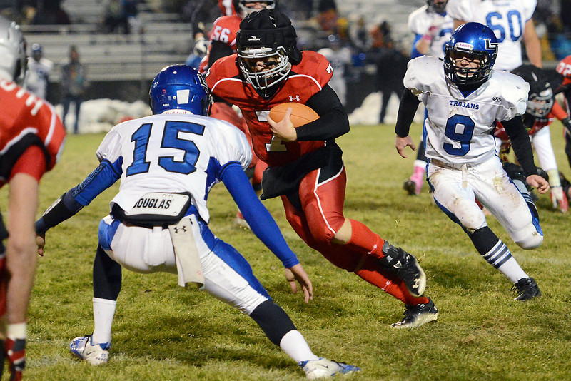Loveland High School quarterback Graham Weeks (7) runs between Longmont defenders Forrest Wetterstrom (15) and Ian Pomper (9) in the first quarter of their game on Friday, Oct. 26, 2012 at Patterson Stadium.