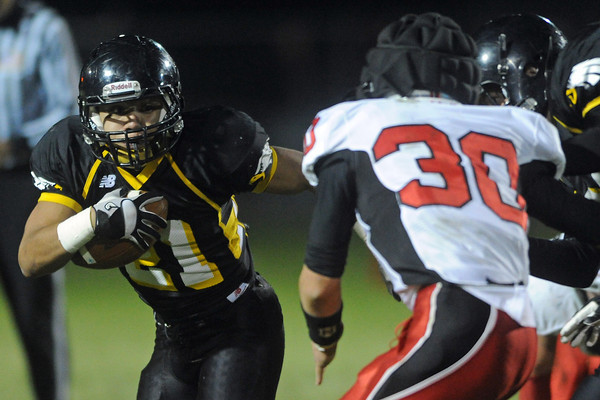 Thompson Valley High School's Francisco Marquez, left, attempts to avoid Loveland defender Jake Weinmaster (30) in the first quarter of their game Friday, Oct. 19, 2012 at Patterson Stadium.
