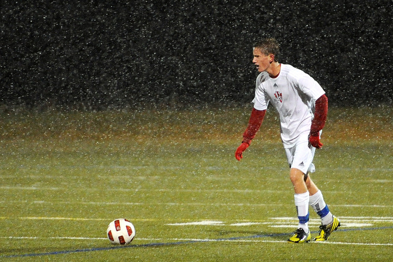 Loveland High School midfielder Brett Peterson looks for an open teammate through the falling snow as he dribbles the ball in the first half of a match against Rock Canyon on Wednesday, Oct. 24, 2012 at the Loveland Sports Park.