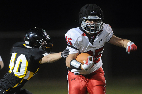 Loveland High School running back Kris Garcia, right, escapes from the grasp of Thompson Valley defender Trent Cooper in the second quarter of their game Friday, Oct. 19, 2012 at Patterson Stadium.