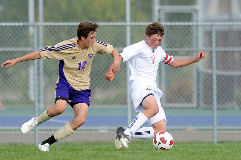 Loveland High School defender Austin Anderson, right, battles with Fort Collins midfielder Derek Poehlmann in the first half of their match on Thursday, Sept 27, 2012 at the Mountain View soccer field.