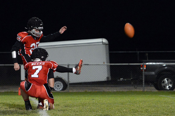 Loveland High School's Brad Parsek (25) kicks an extra point while teammate Graham Weeks (7) holds in the first quarter of a game against Greeley West on Thursday, Oct. 4, 2012 at Patterson Stadium.