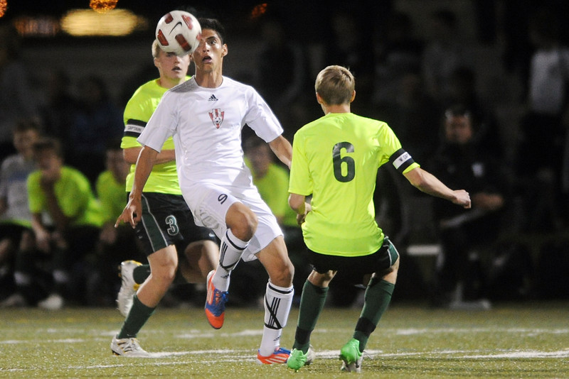 Loveland High School's Cristian Buendia, middle, tracks down the ball between Fossil Ridge's Hunter Robinson, back, and Nate Blank in the first half of their match on Tuesday, Oct. 16, 2012 at the Loveland Sports Park.