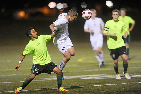 Loveland High School forward Nicholas Grindy (12) heads the ball out of the air in front of Fossil Ridge's Delfino Balderas (11) in the first half of their match on Tuesday, Oct. 16, 2012 at the Loveland Sports Park.
