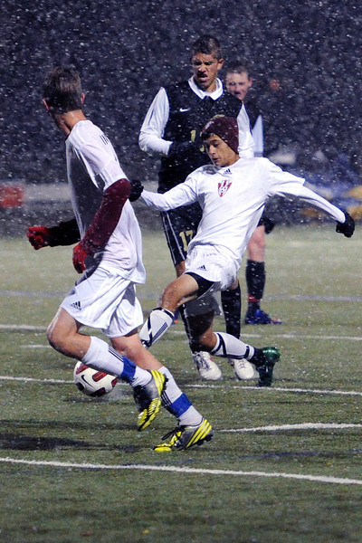 Loveland High School freshman Adrian Cordova, right, passes the ball to teammate Brett Peterson in the first half of a match against Rock Canyon on Wednesday, Oct. 24, 2012 at the Loveland Sports Park.
