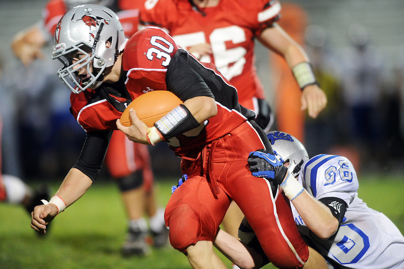 Loveland HIgh School running back Jake Weinmaster (30) is pulled down by Broomfield defender Dan Perse in the second quarter of their game Thursday, Sept. 13, 2012 at Patterson Stadium.