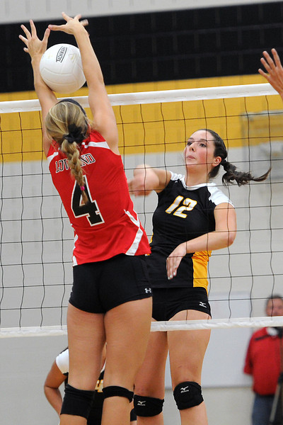 Thompson Valley High School junior Emily Newton (12) attempts to spike the ball past Loveland's Kim Weissmann during set one of their match Friday, Aug. 31, 2012 at TVHS.