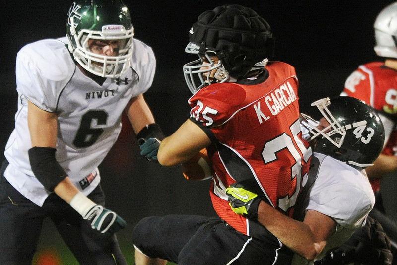 Loveland High School running back Kris Garcia (35) is tackled by Niwot's Danny Caruso on a carry in the first quarter of their game on Friday, Sept. 28, 2012 at Patterson Stadium.