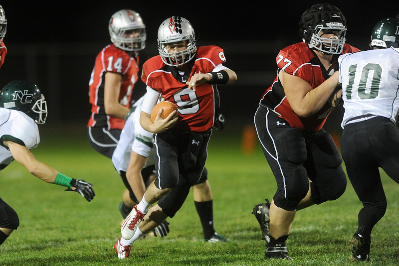 Loveland High School quarterback Mike Zweigle (9) makes a run behnd the block of teammate Eric Woodward (77) in the first quarter of a game against Niwot on Friday, Sept. 28, 2012 at Patterson Stadium.