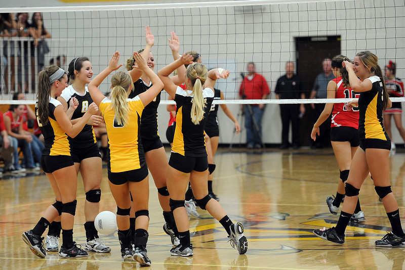 Thompson Valley High School volleyball players celebrate after winning a point in set two of a match against Loveland on Friday, Aug. 31, 2012 at TVHS.