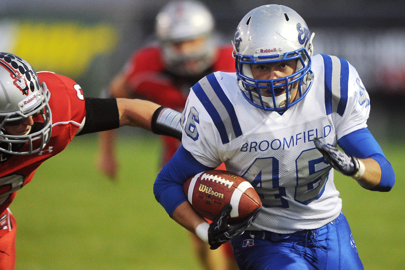 Broomfield High School's D.J. Zissimos (46) runs after a catch while Loveland defensive back Greg Hecker, left, gives chase in the first quarter of their game Thursday, Sept. 13, 2012 at Patterson Stadium.