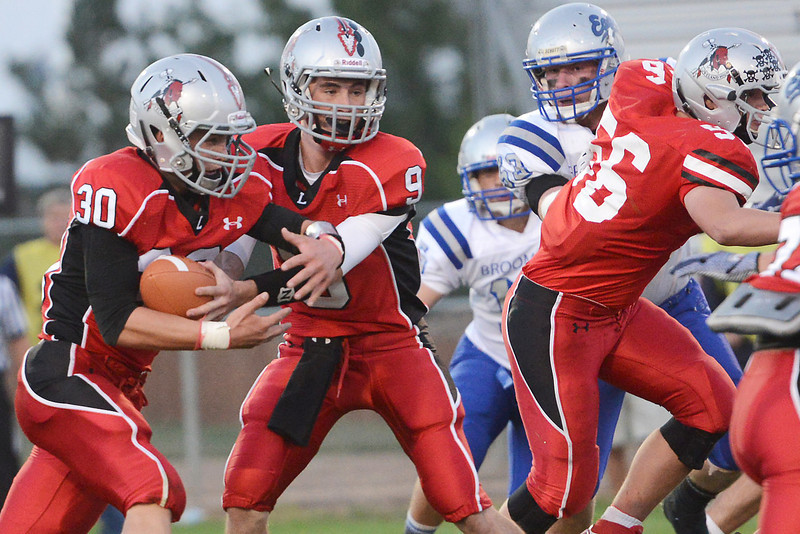 Loveland HIgh School running back Jake Weinmaster (30) takes a handoff from quarterback Mike Zweigle (9) in the first quarter of their game against Broomfield on Thursday, Sept. 13, 2012 at Patterson Stadium.