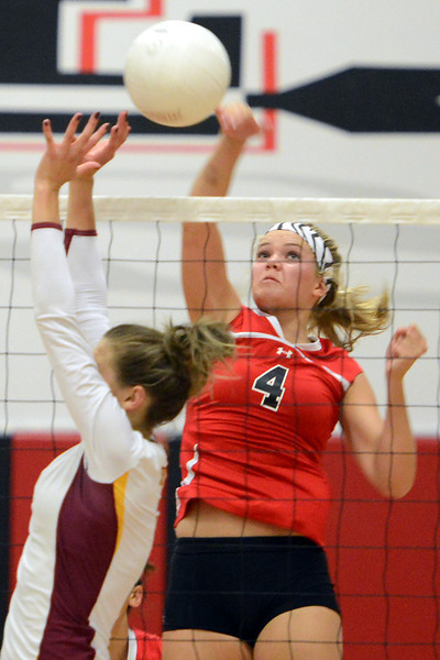 Loveland High School junior Kim Weissmann spikes the ball over Rocky Mountain's Hanna Wiggins during set one of their match on Tuesday, Sept. 25, 2012 at LHS.