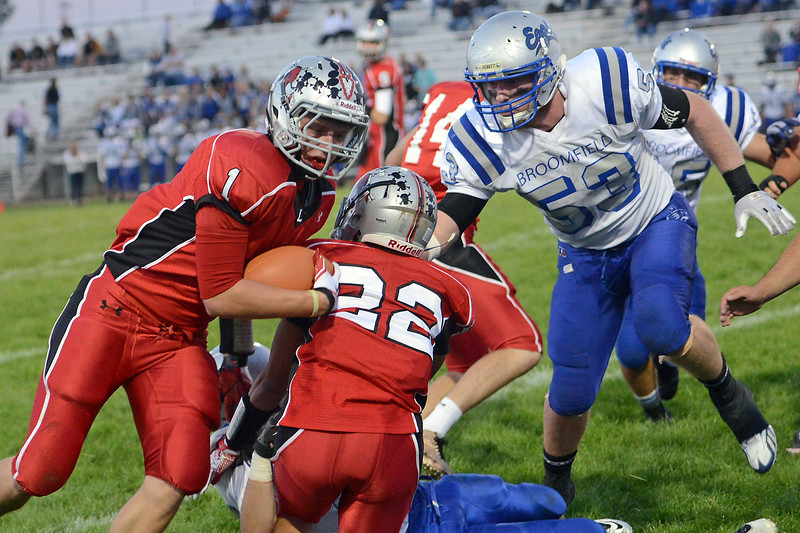 Loveland HIgh School running back Ryan McCloughan (1) is pursued by Broomfield defensive lineman Andrew McLean (53) on a run play in the first quarter of their game Thursday, Sept. 13, 2012 at Patterson Stadium.