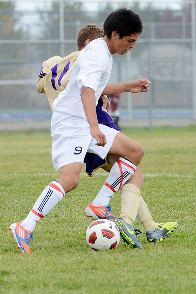 Loveland High School senior Cristian Buendia (9) battles for control of the ball against Fort Collins' Max Arellano during the first half of their match on Thursday, Sept 27, 2012 at the Mountain View soccer field.