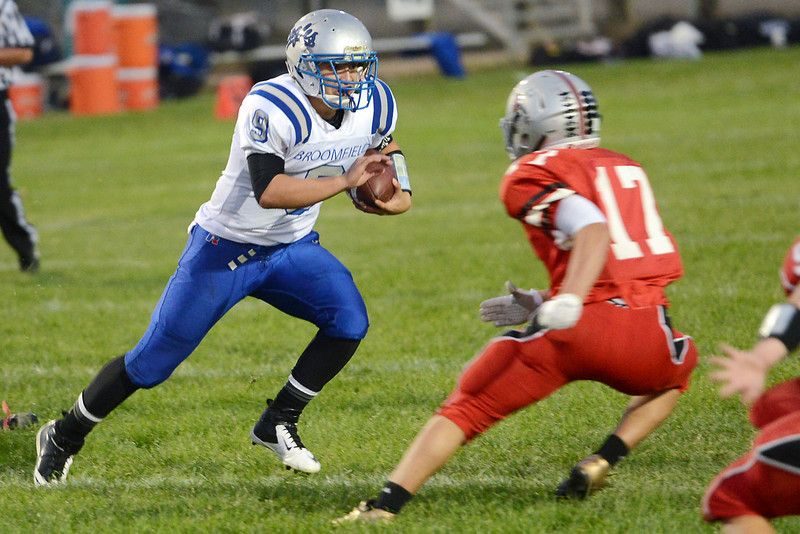 Broomfield High School quarterback Angelo Perez (9) rushes for a touchdown around Loveland defender Mitchell Wheelock in the first quarter of their game Thursday, Sept. 13, 2012 at Patterson Stadium.