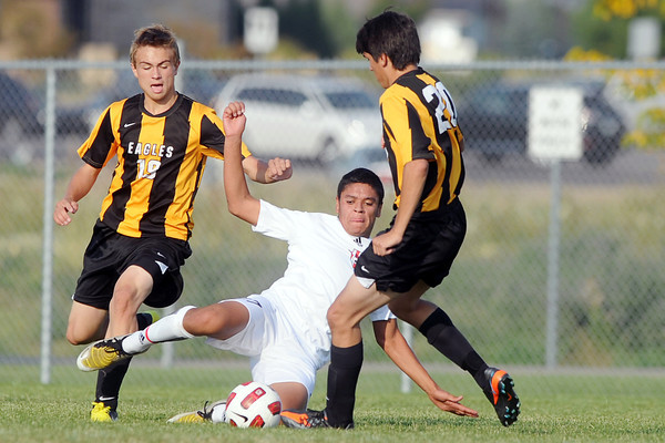 Loveland High School's Marco Gonzalez slides between Thompson Valley's Tanner Wall, left, and Joshua Shultz as the players fight for control of the ball in the first half of their match on Friday, Sept. 21, 2012 at the Mountain View soccer field.