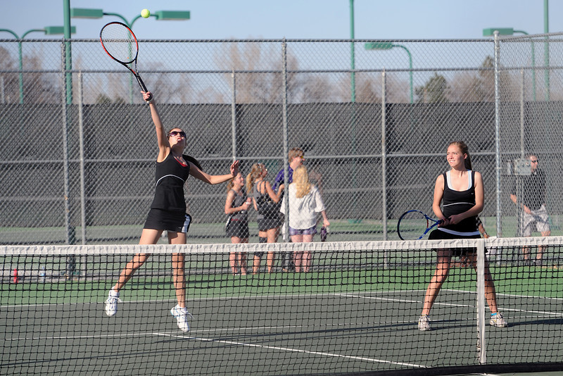 Loveland High School's Ashlyn Wong, left, hits an overhead smash while her No. 1 doubles teammate Joelle Foster looks on during their match against Mountain View's Taylor Lang and McKenna Epperson on Thursday, March 15, 2012 at LHS.