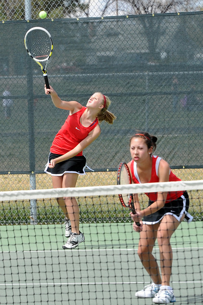 Loveland High School's Katie Nottberg, left, hits a serve while her No. 2 doubles partner Ashlyn Wong plays at the net during the Northern Colorado Invitational on Friday, April 13, 2012 at LHS.