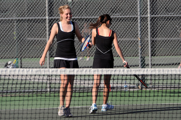 Loveland High School senior Joelle Foster, left, shares a laugh with her No. 1 doubles partner Ashlyn Wong during their match against Mountain View's Taylor Lang and McKenna Epperson on Thursday, March 15, 2012 at LHS.