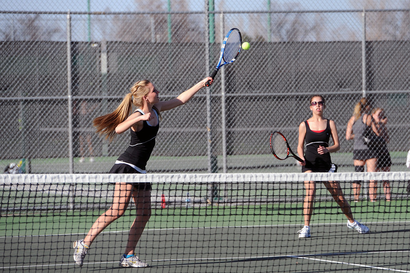 Loveland High School's Joelle Foster, left, hits a volley at the net while her No. 1 doubles teammate Ashlyn Wong looks on during their match against Mountain View's Taylor Lang and McKenna Epperson on Thursday, March 15, 2012 at LHS.