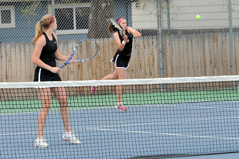 Loveland High School's Sarah Clinkenbeard, right, returns a shot while her No. 1 doubles partner Kim Weissmann looks on during their match Friday, March 30, 2012 against Thompson Valley's Emily Erickson and Samantha Sheets at TVHS.