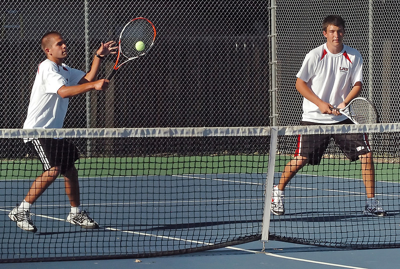 Loveland High School's Zach Geroche, left, hits a volley at the net while Jesse Jacobson looks on during their No. 3 doubles match against Thompson Valley on Thursday, Sept. 2, 2010 at TVHS.