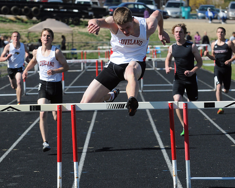 Loveland High School senior Casey Riggs clears the final hurdle on his way to a win in the 300-meter hurdles Friday for the R2-J Invitational at the LHS track.
