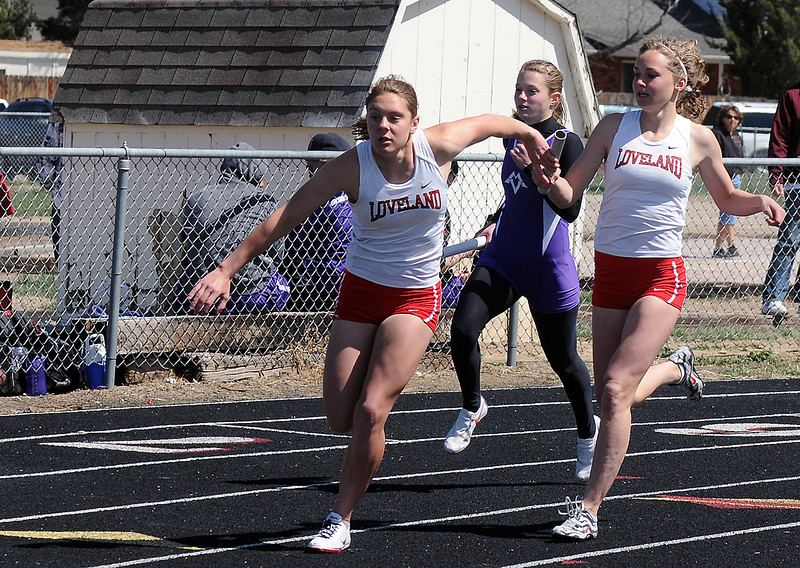 Loveland High School freshman Taylor Buschy, right, passes the baton to sophomore Michal Bower during the 800 meter relay during R2-J Invitational on Friday at the LHS track.