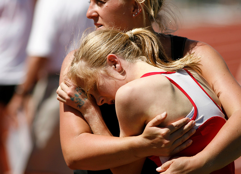 Loveland High school girl is held up by CHSSA medical staffer, Lisa Porter, after the the 5A 1600