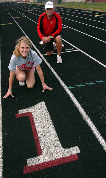 Loveland High School track athlete Steph Hutsell, left, and coach Rod Staggs pose for a photo on the track Monday afternoon.