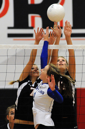 Loveland High School senior Kendahl Holley, background, left, and junior Katie Dotson block an attempt by junior Kyra Aragon of Thornton High School during the first game of Wednesday night's match at Loveland High School.